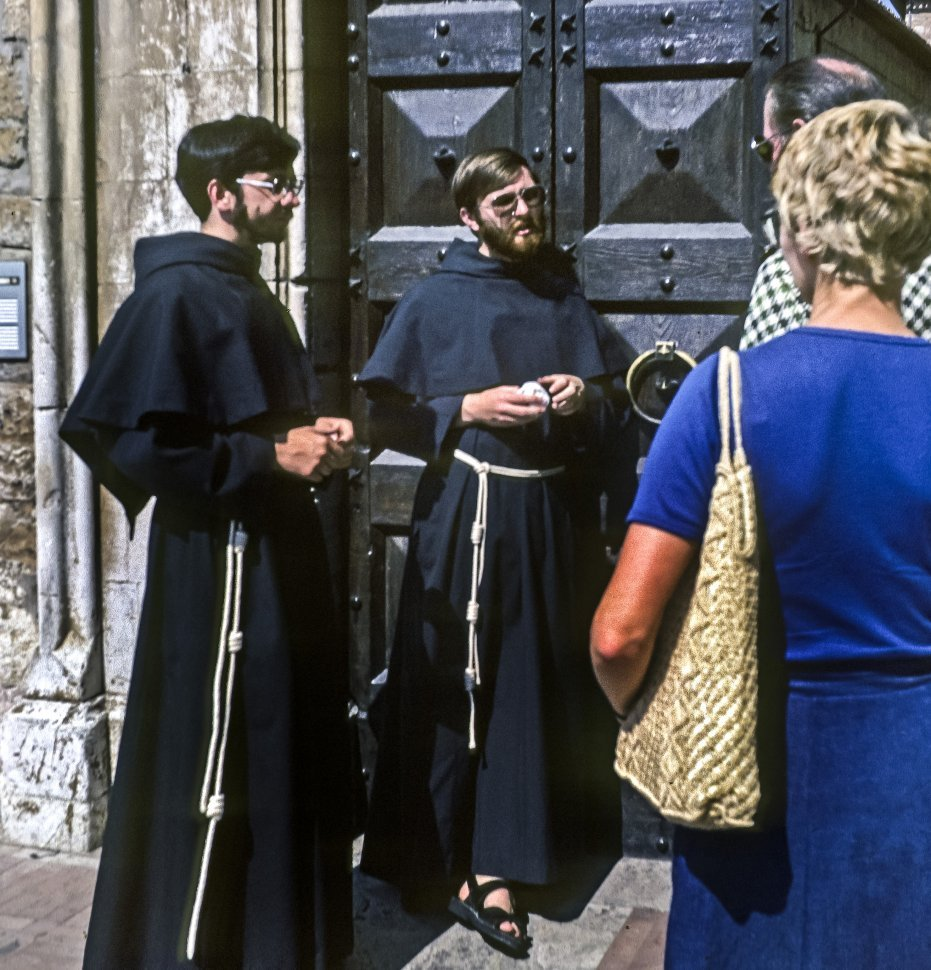 Free image of Monks speaking to people on the street.