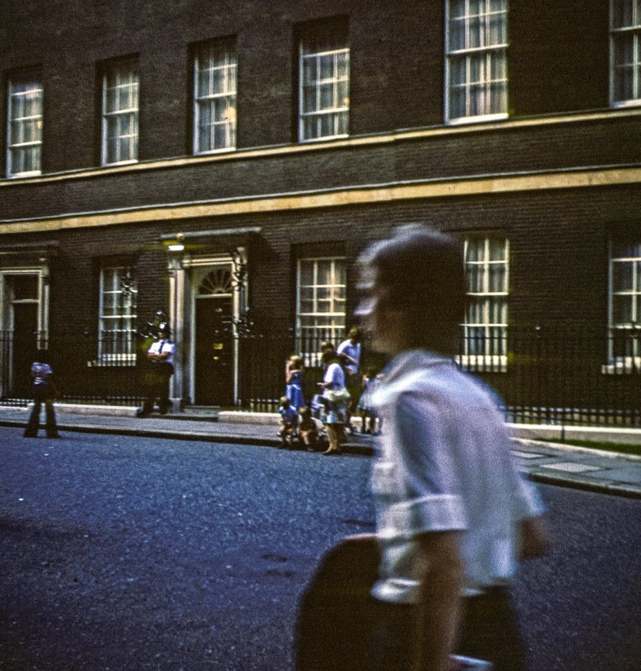 Free image of Group of people walking through the street in front of a guarded building.