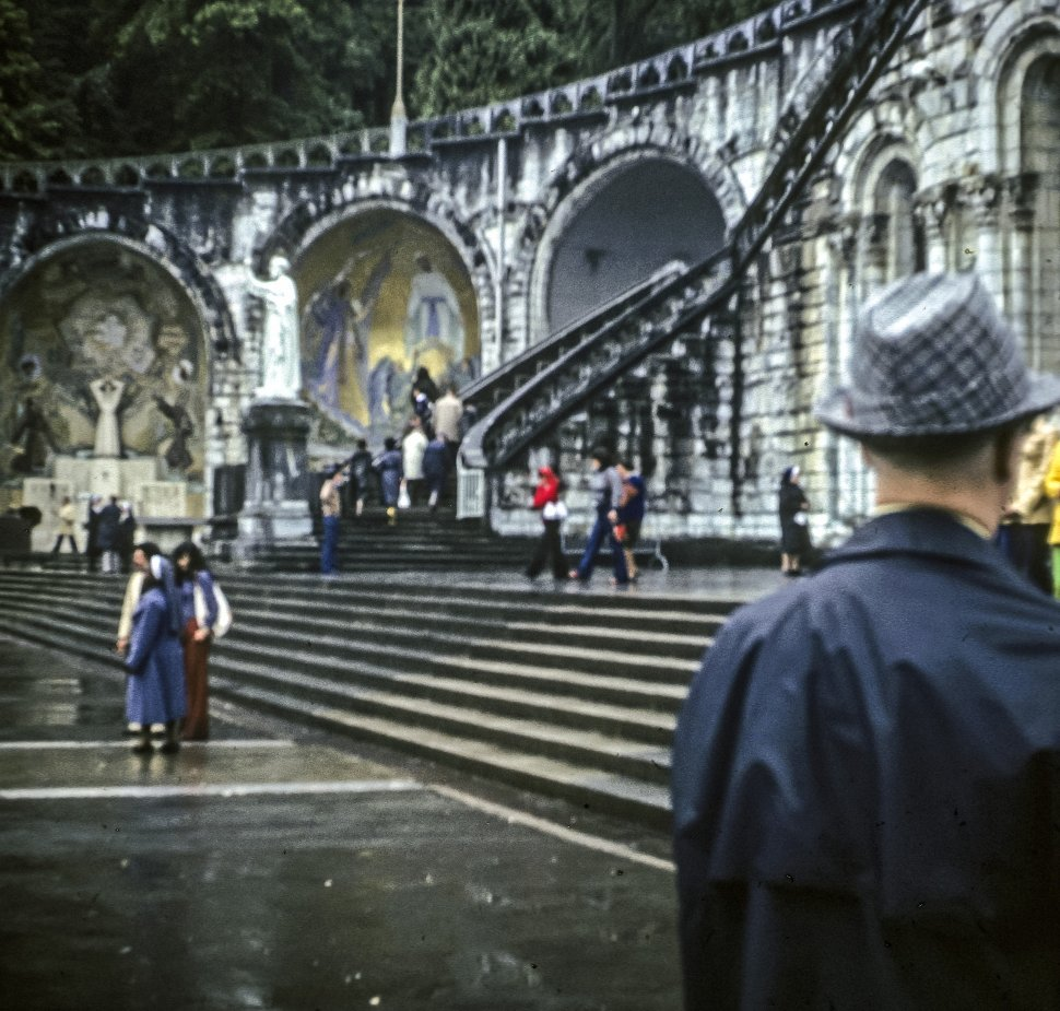 Free image of Group of tourists walking around a courtyard in front of a statue on a rainy day.