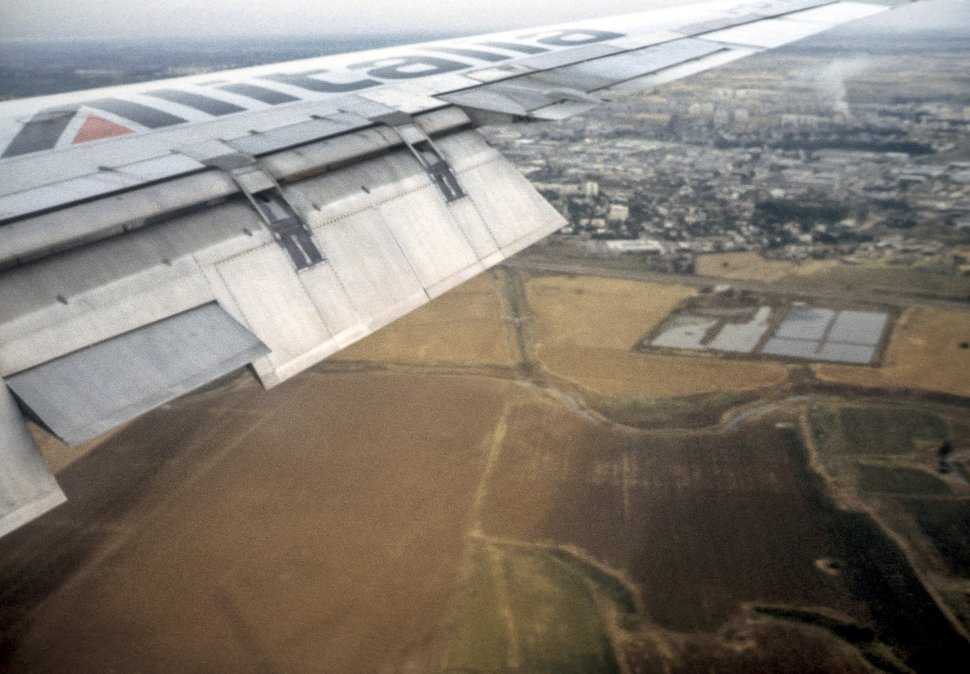Free image of View out an airplane window of the wing and the ground below.
