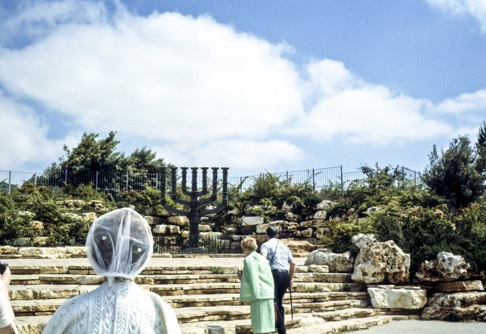 Free image of Tourists visiting a sculpture of a large Menorah, Israel