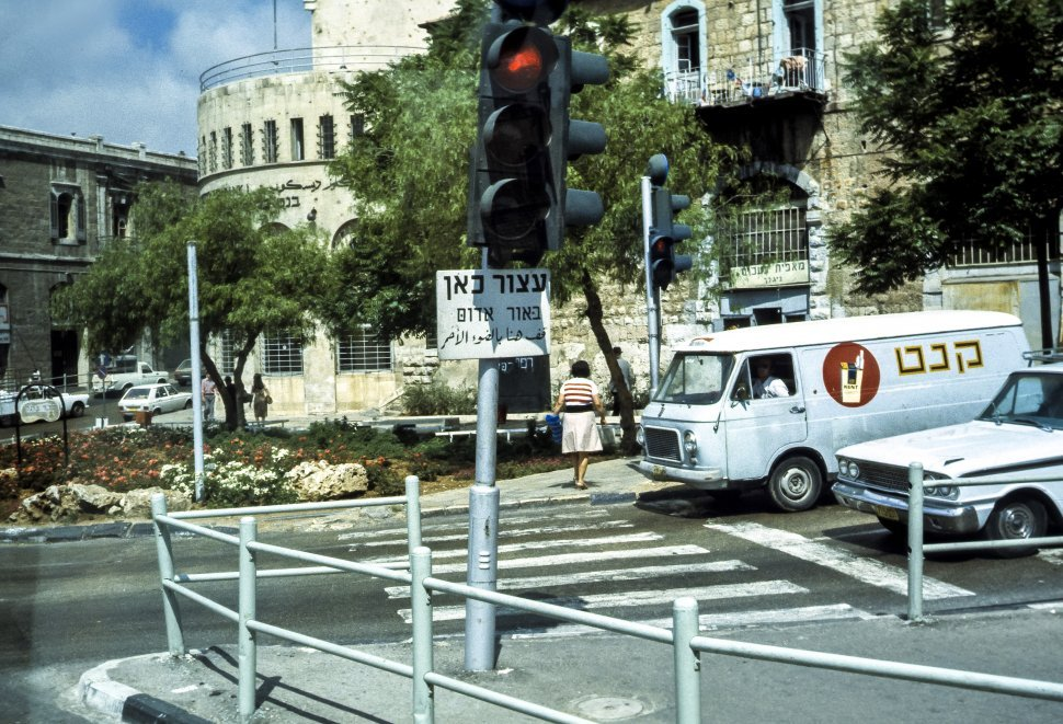 Free image of Woman crossing a street in the crosswalk with traffic stopped, Israel