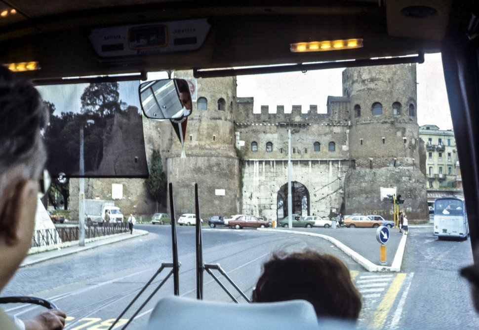 Free image of Image through a tour bus window of a castle and street, Europe