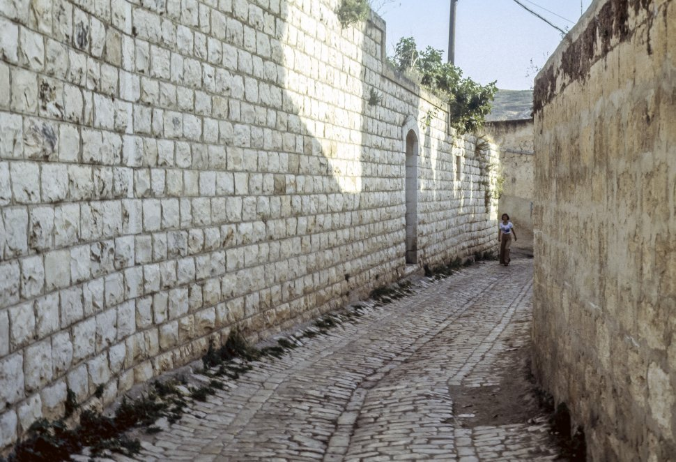 Free image of Woman walking alone down a cobblestoned alley.
