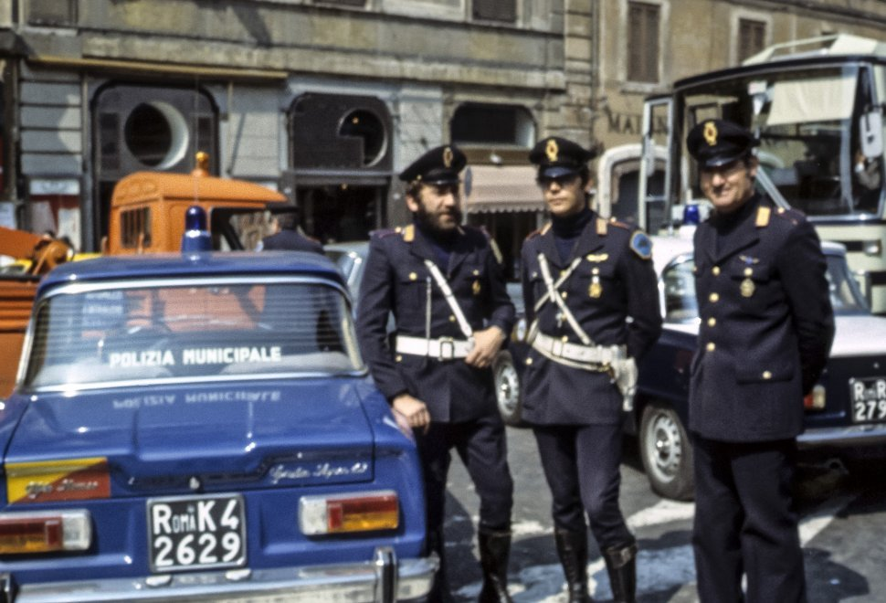 Free image of Three policemen standing in traffic smiling.