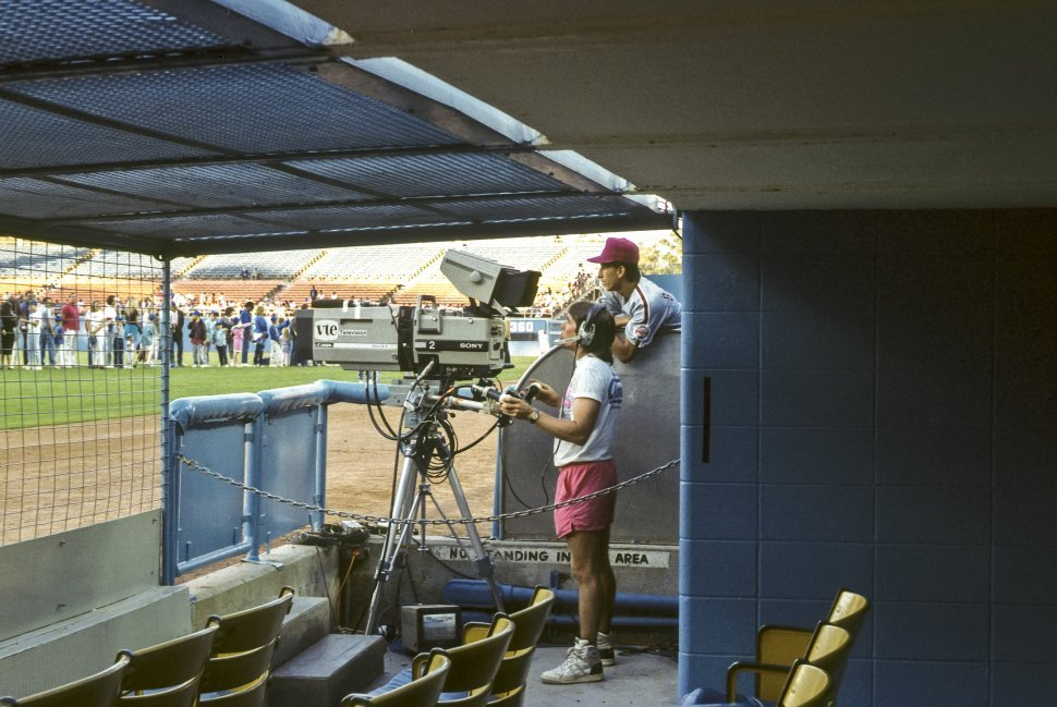 Free image of Camera man and player in the dugout of a baseball field with fans in the background.