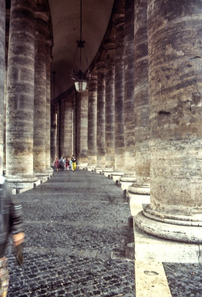 Free image of Stone columns lining a walkway with a group of people walking.