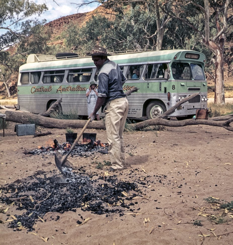 Free image of Man stoking a campfire next to a tour bus and tourist.
