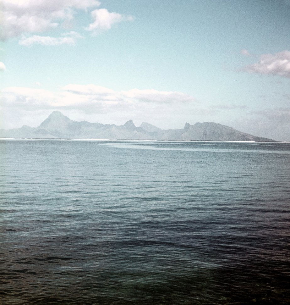 Free image of Mountains rolling behind a bay.