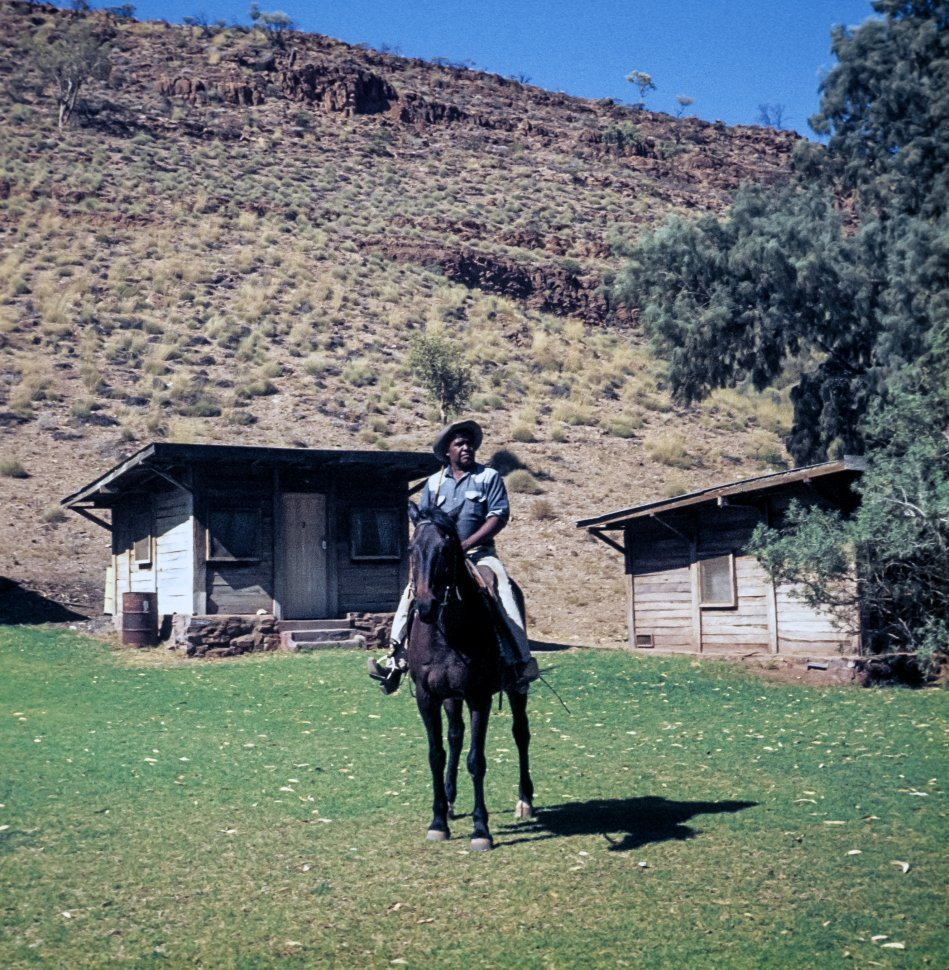 Free image of Man riding his horse in front of cabins on a farm.