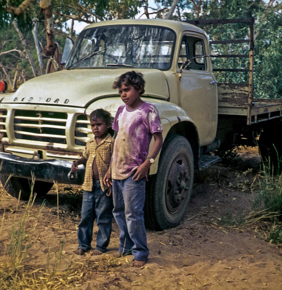 Free image of Two barefoot children posing in front of a vintage truck.