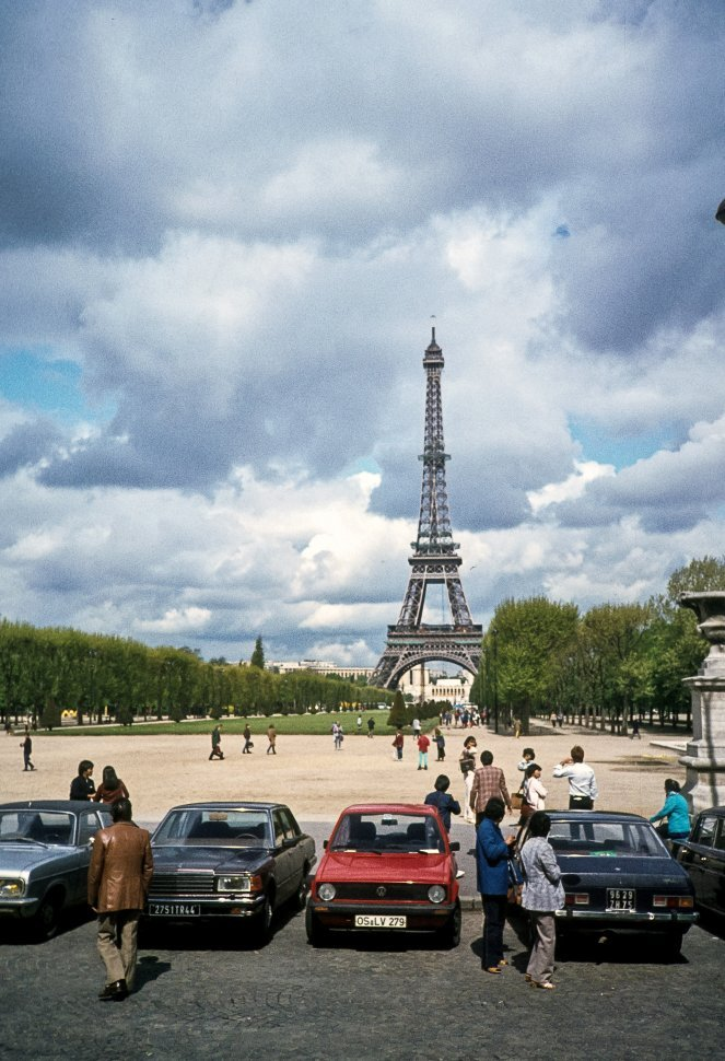 Free image of Crowd milling about the parking lot and courtyard below the Eiffel Tower, Paris, France