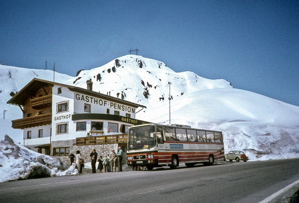 Free image of Tourists coming off a tour bus on the side of a snowy mountain.