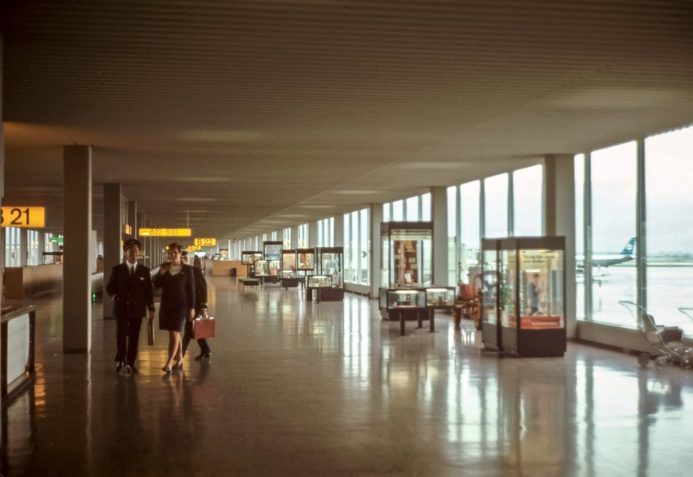 Free image of Two people walking down the walkway past windows and planes on the runway.