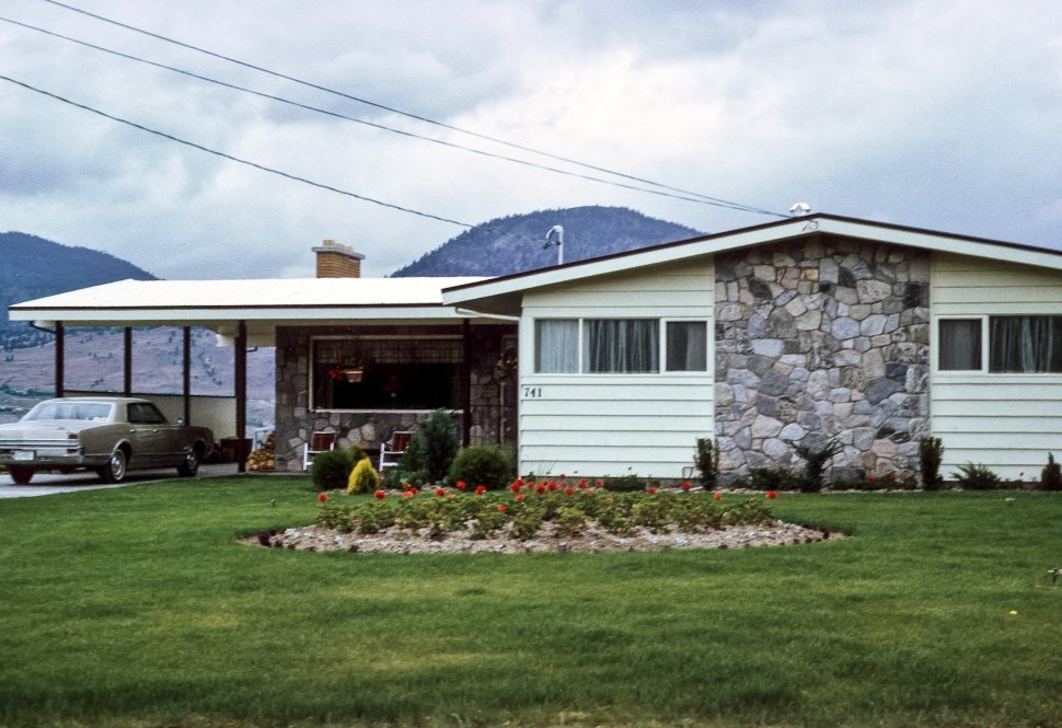 Free image of Suburban home and carport with hills in background.