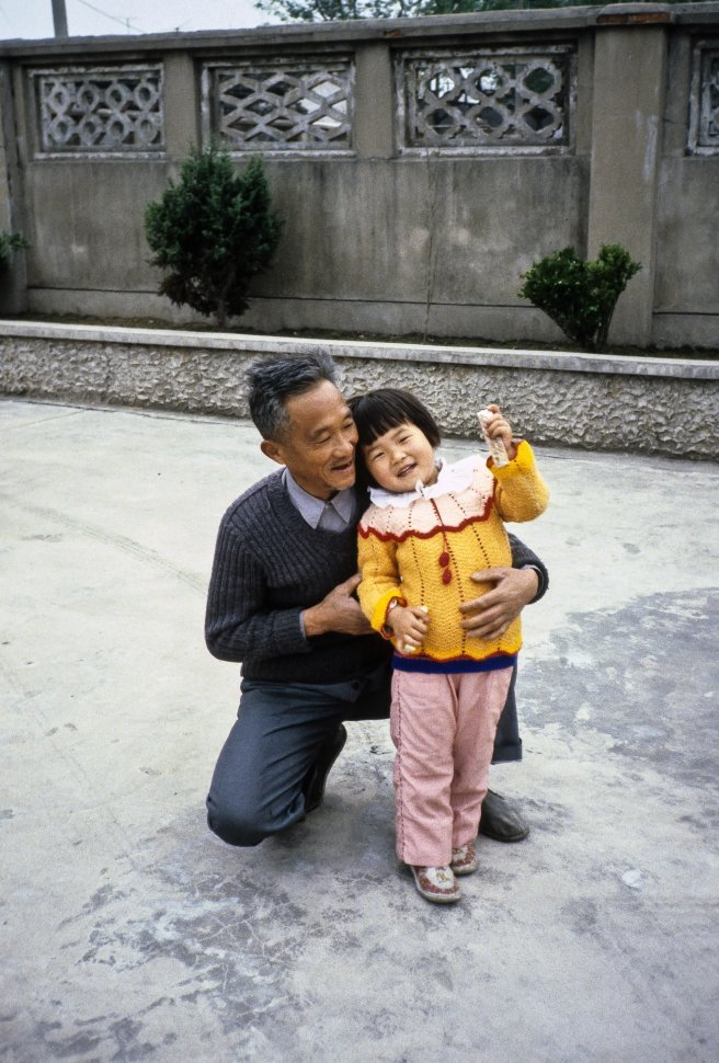 Free image of Man and child smiling and waving at camera, Asia