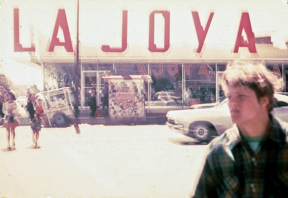 Free image of Blurry photograph of a sign saying La Joya, and people walking down the street.