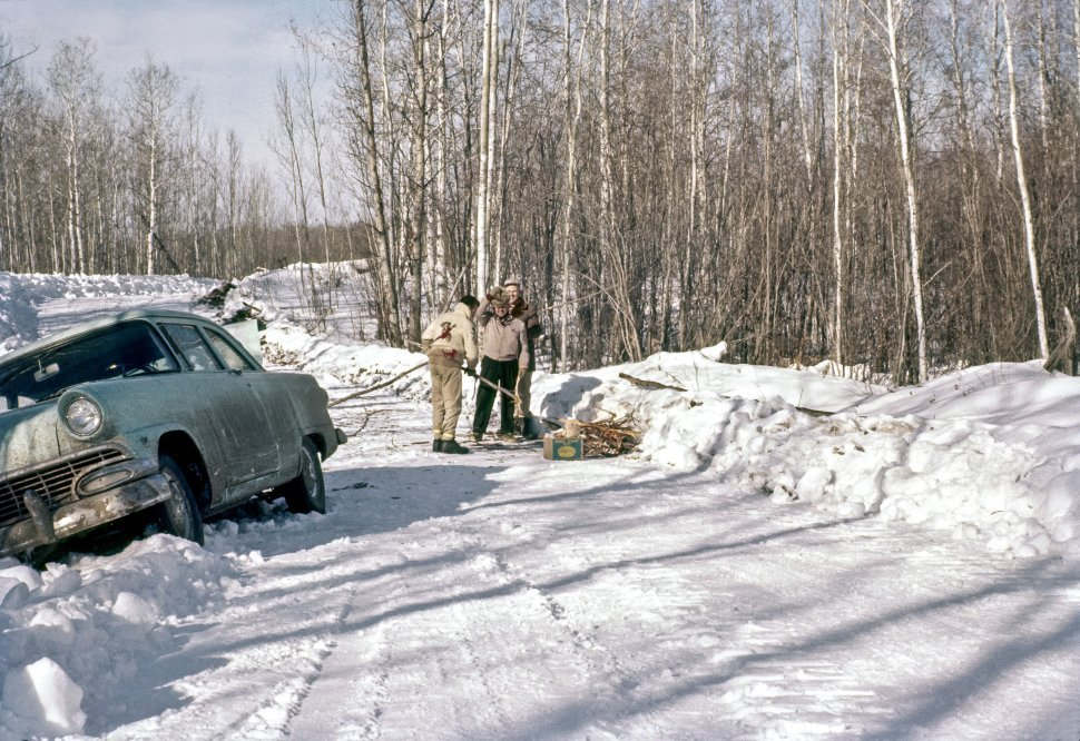 Free image of Three men gathering firewood on a snowy forest road near car stuck in snowbank.