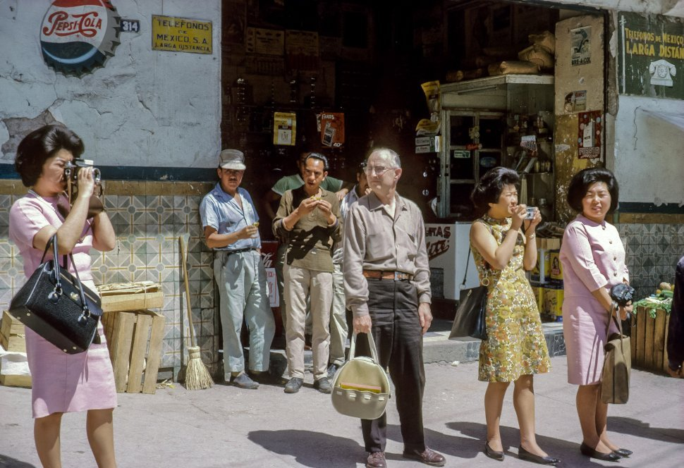 Free image of Group of tourists taking photographs on the street, Mexico
