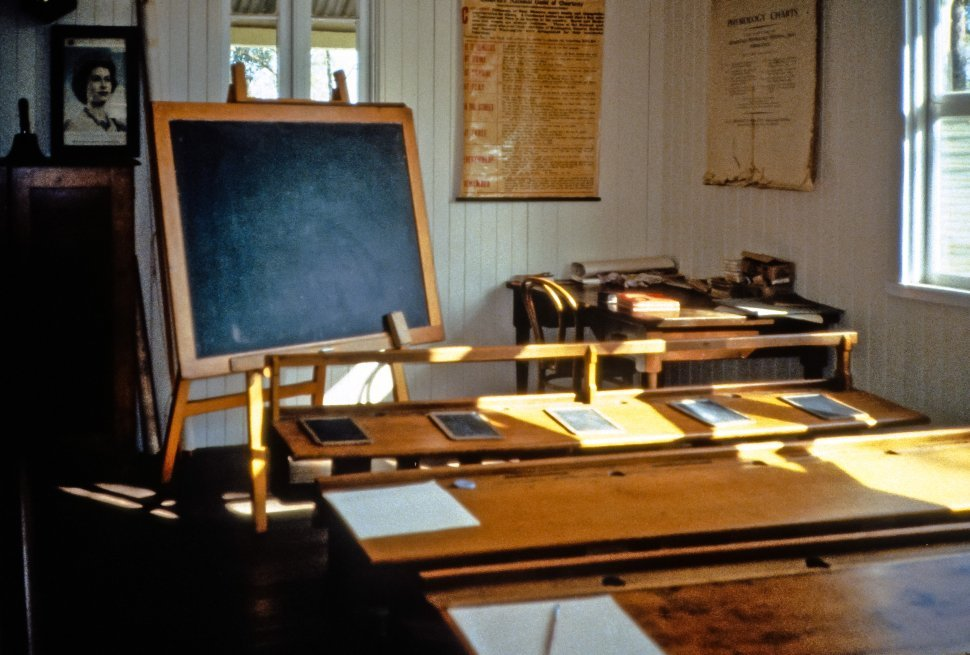 Free image of Old fashioned school room with desks and blackboard.