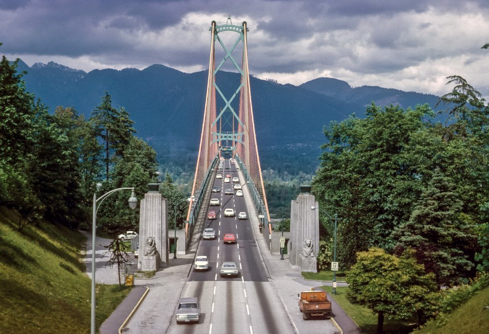 Free image of Traffic driving across a scenic bridge on a cloudy day. The Lions Gate Bridge, opened in 1938, officially known as the First Narrows Bridge, is a suspension bridge that connects the City of Vancouver, British Columbia to the North Shore municipalities of the District of North Vancouver, the City of North Vancouver, and West Vancouver.