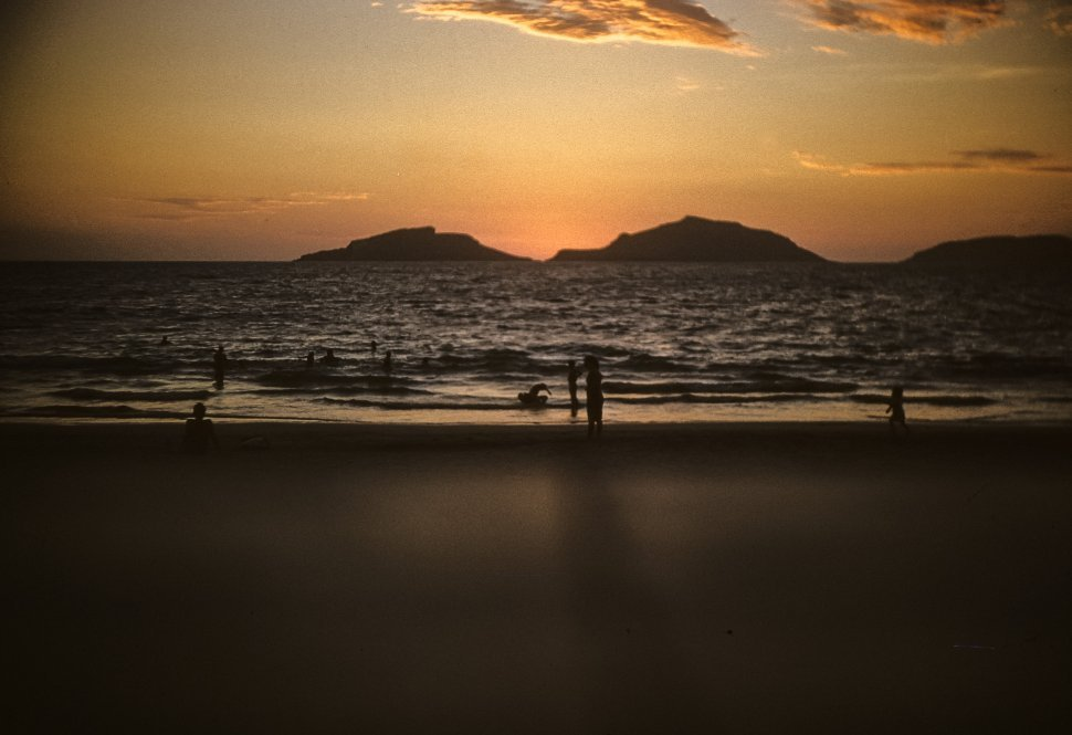 Free image of People swimming in the ocean with a beautiful sunset behind the hills.