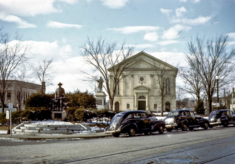 Free image of Vintage cars parked along a snowy roadside with columned building and statues behind them.