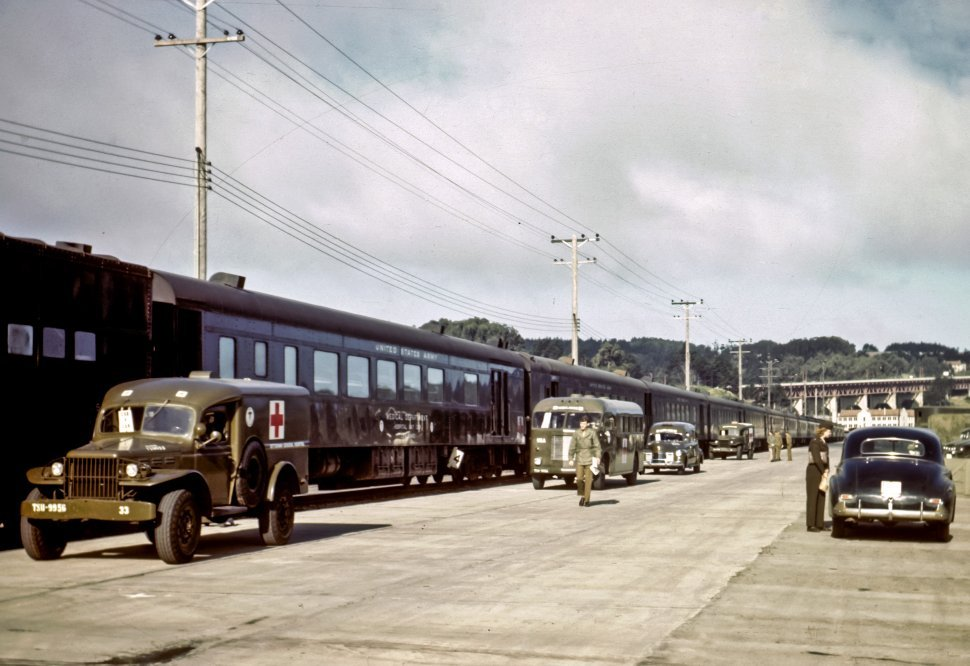Free image of Train and red cross truck with military personnel.