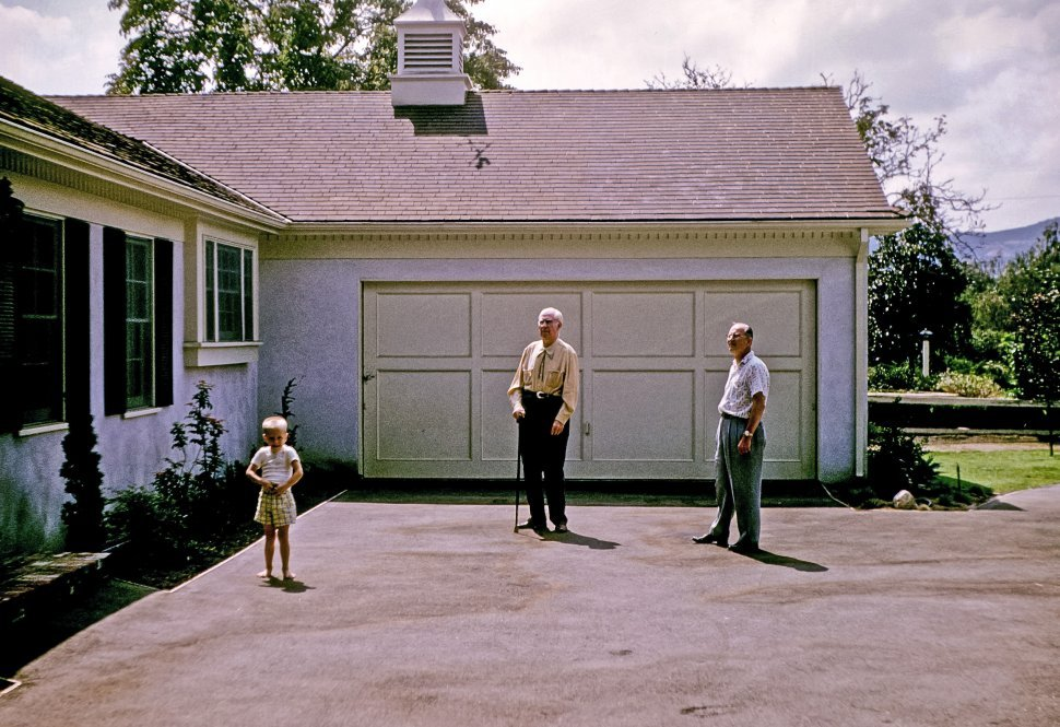 Free image of Two men and a little girl standing in the driveway in front of a suburban home, USA