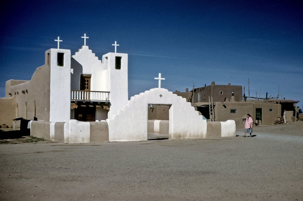 Free image of Native American woman walking from a pueblo to a catholic church, Taos, New Mexcio, USA