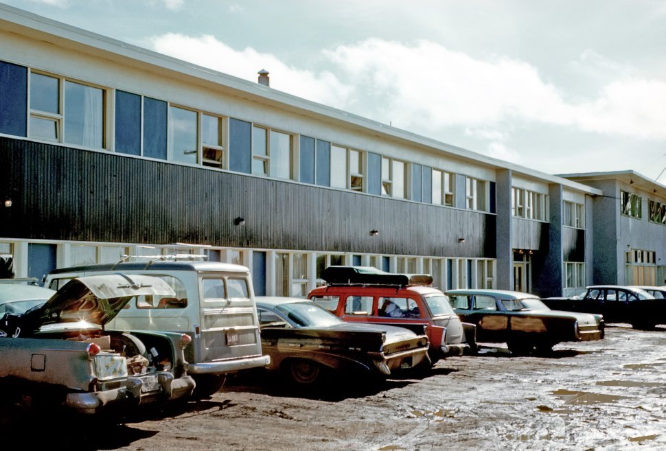 Free image of Muddy parking lot and cars in front of a motel, USA