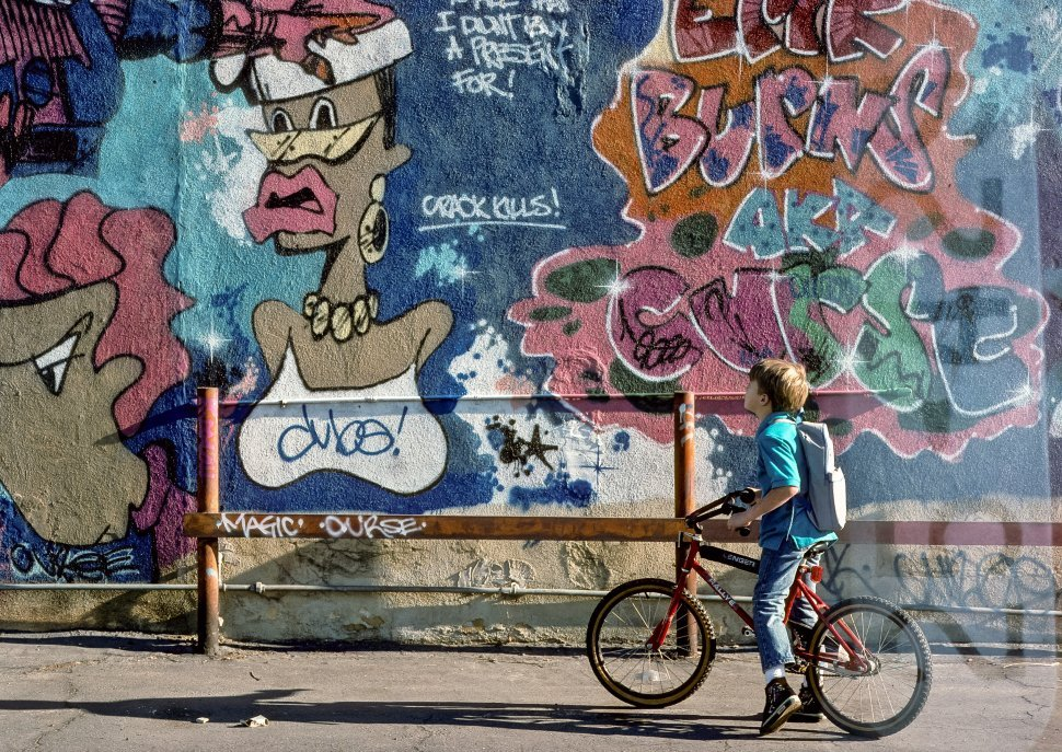 Free image of Child on a bicycle looking up at graffiti on the street, USA