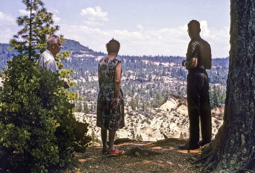 Free image of Three people looking out over canyon, USA