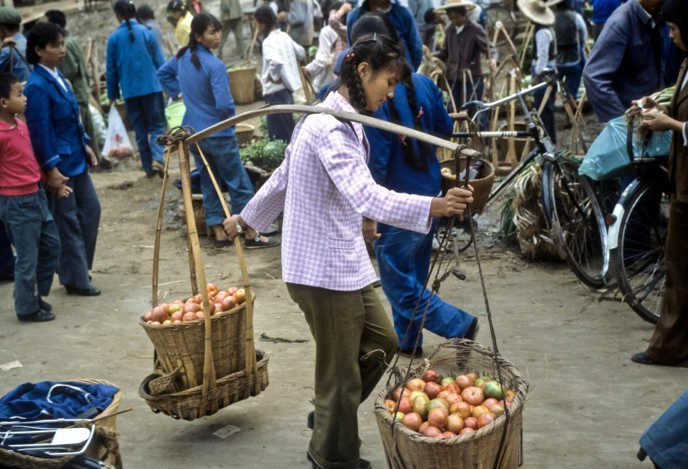 Free image of People carrying apples in baskets balanced on their shoulders marketplace, China