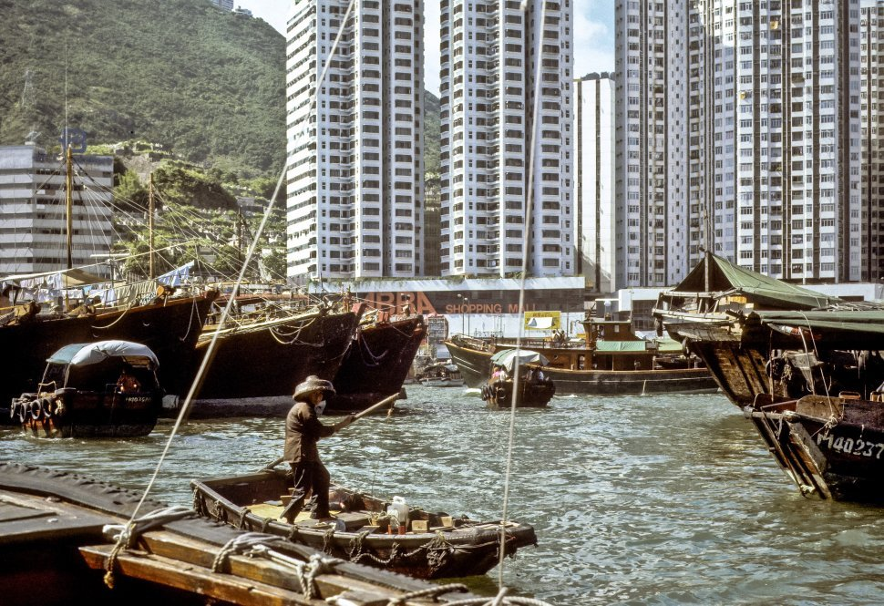 Free image of Man paddling a boat through a harbor in front of skyscrapers, Hong Kong, China