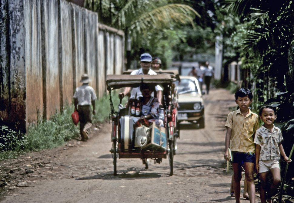 Free image of Man giving someone a ride in a rickshaw, while children smile at the camera, Asia