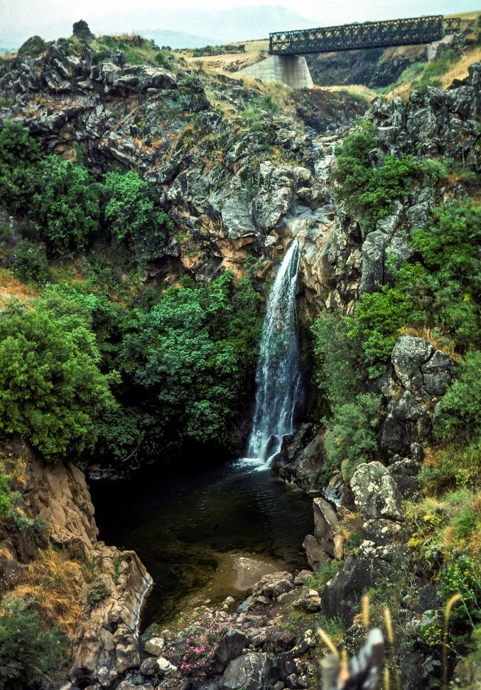 Free image of Waterfall going over a small cliff into a pool.