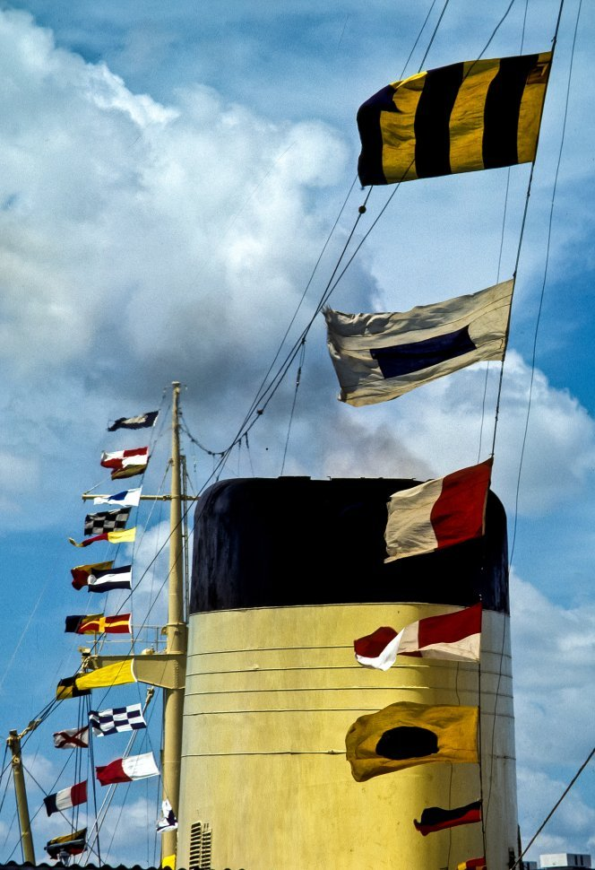 Free image of Smokestack of a cruise ship and flags in the wind.