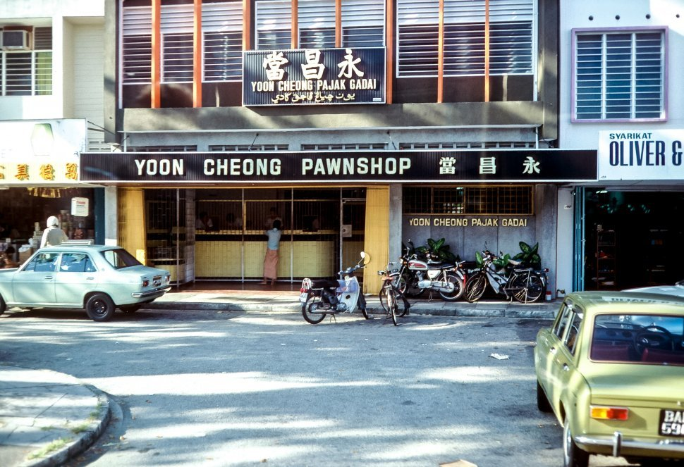 Free image of Motorcycles parked on a city street in front of a pawnshop, Asia