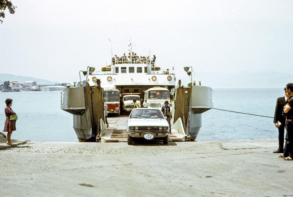 Free image of Cars driving off a ferry boat into a village beach, with tourists waiting.