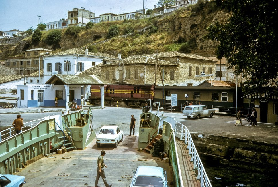 Free image of Cars driving off a ferry boat into village.