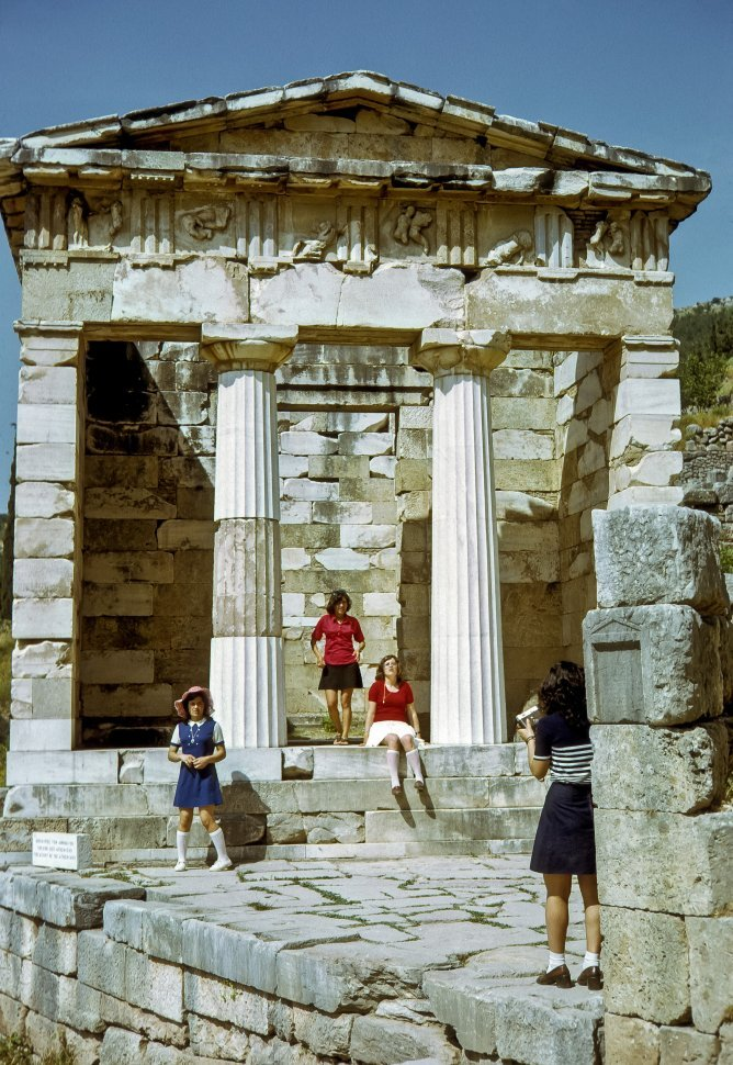 Free image of Three girls posing for a photograph in front of ancient ruins, Greece