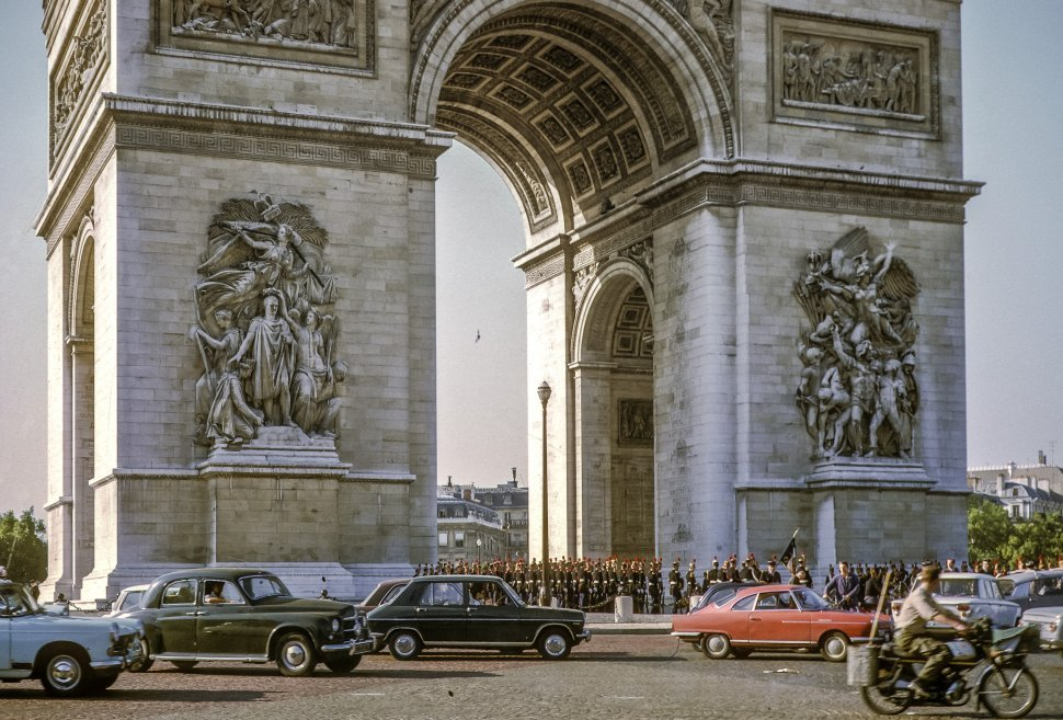 Free image of Arc de Triomphe behind moving traffic with a parade moving through, Paris, France