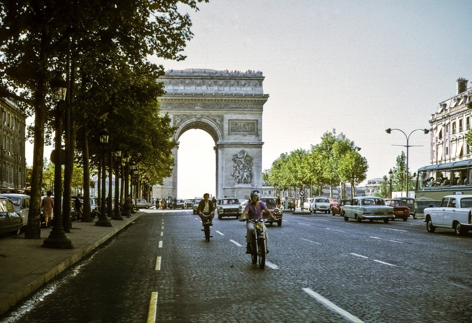 Free image of Arc de Triomphe behind moving traffic on a tree lined street, Paris, France