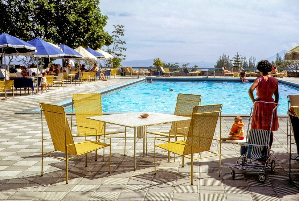 Free image of Family playing at poolside of a hotel.