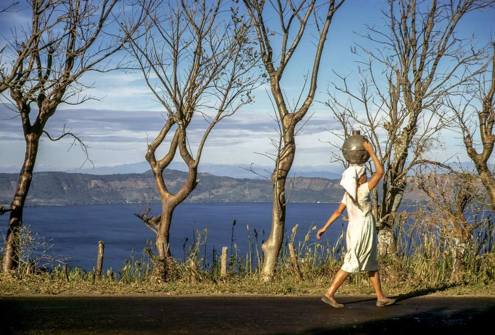 Free image of Local woman walking with a large jar of water on her head past a lake.