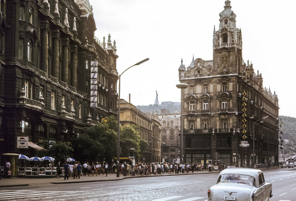 Free image of Car driving past a crowd of people, moving past buildings and outdoor restaurants at Ferenciek square, Budapest, Hungary