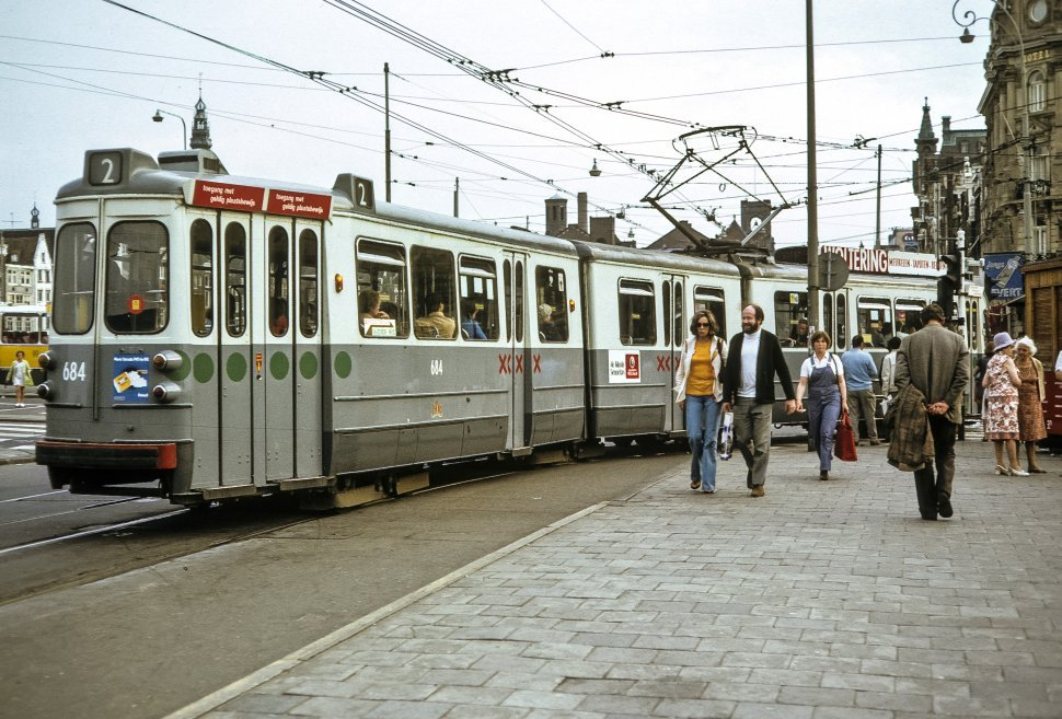 Free image of People moving through city streets and people riding trolley cars, Amsterdam, Netherlands.