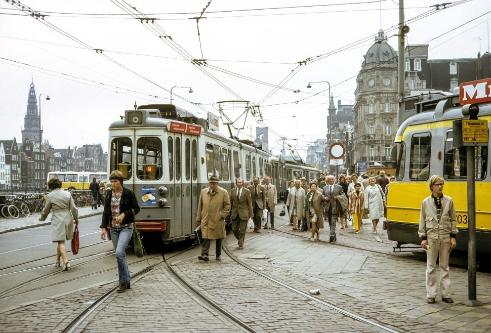 Free image of Crowds moving through city streets and trolley cars, Amsterdam, Netherlands.