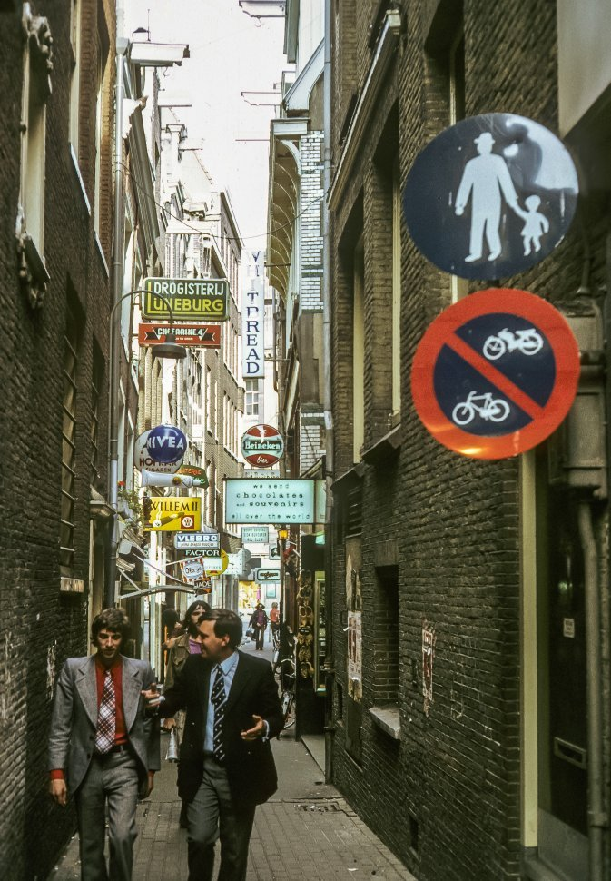Free image of Two men talking and walking down a small alley full of shops, Europe